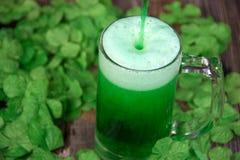 Зеленое пиво в кружке с shamrocks Стоковое Фото