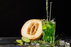 Зеленое питье с известкой и астрагоном Коктеиль и дыня на черной предпосылке Здоровые, сладостные и вкусные пить скопируйте космо Стоковая Фотография