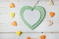 Зеленое сердце в круге меньших оранжевых и желтых сердец на деревянной предпосылке Стоковое фото RF