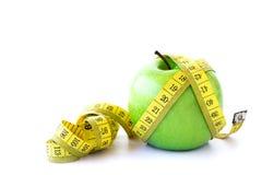 Зеленое яблоко и измеряя лента на белой предпосылке Стоковые Изображения RF