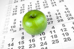 Зеленое яблоко на листах календаря стены Стоковая Фотография