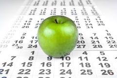 Зеленое яблоко на листах календаря стены Стоковые Изображения