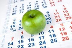 Зеленое яблоко на листах календаря стены Стоковая Фотография RF