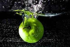 Зеленое яблоко падает внутри для того чтобы намочить Стоковые Изображения RF
