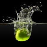 Зеленое яблоко падая в воду на черной предпосылке Стоковое Изображение RF