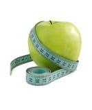 Зеленое яблоко с измеряя лентой на белой предпосылке Стоковая Фотография RF