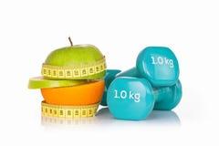 Зеленое яблоко с измеряя лентой с парой голубых гантелей фитнеса Стоковые Изображения