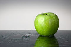 Зеленое яблоко с падением воды Стоковое Фото
