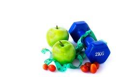 Зеленое яблоко, dumbbelle и измеряя лента на белой предпосылке Стоковая Фотография RF