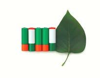 зеленые батареи щелочных аккумуляторов с лист над белой предпосылкой Стоковые Фотографии RF