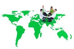 Зеленые бизнесмены держа руки на зеленом мире Стоковая Фотография