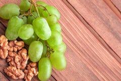 Зеленые виноградины и грецкий орех на деревянном столе Стоковые Изображения