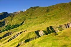 Зеленые горные склоны на предпосылке голубого неба Стоковое Изображение