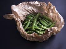 Зеленые горохи в коричневой бумаге изолированной на черноте Стоковые Фото