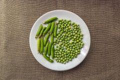 Зеленые горохи на белой плите Стоковое фото RF