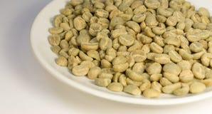 Зеленые зерна кофе на белой плите на белой предпосылке Стоковое Изображение RF
