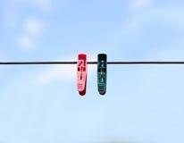 Зеленые и красные зажимки для белья на веревочке На предпосылке сини Стоковое Фото