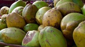 Зеленые кокосы штабелированные на ` s поставщика обочины ходят по магазинам Стоковое фото RF