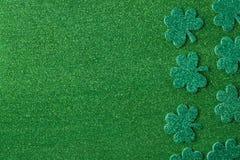 Зеленые клевера или Shamrocks на зеленой предпосылке предпосылки Стоковая Фотография RF