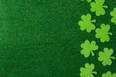 Зеленые клевера или Shamrocks на зеленой предпосылке Стоковое Фото
