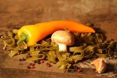 Зеленые макаронные изделия с ингридиентами на каменной предпосылке Стоковые Фото