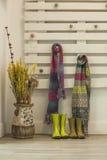 Зеленые ненастные ботинки и красочные шарфы вися в стене паллета Стоковое Изображение RF