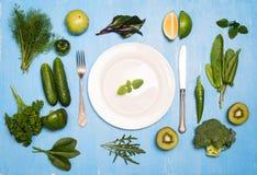 Зеленые овощи приносить и травы вокруг белых плиты и silverwa Стоковое Изображение RF