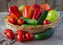 Зеленые огурцы, красные томаты и сладостные перцы в деревянный лежать корзины Стоковая Фотография
