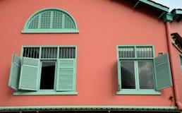 Зеленые окна на стене красного цвета земли стоковое фото