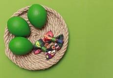 Зеленые пасхальные яйца с красочным смычком зеленый цвет пасхи предпосылки Co стоковое фото rf