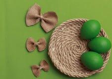 Зеленые пасхальные яйца с красочным смычком зеленый цвет пасхи предпосылки Co стоковые фотографии rf