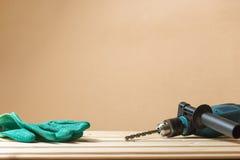 Зеленые работая перчатки с бурильным молотком на деревянном столе и экземпляре подкладки размечают предпосылку Концепция работник Стоковые Изображения RF