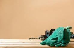 Зеленые работая перчатки с бурильным молотком на стене деревянного стола подкладки и космоса экземпляра Концепция работников защи Стоковые Изображения RF