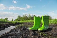Зеленые резиновые ботинки в грязи рядом с лужицей на влажной проселочной дороге Стоковая Фотография