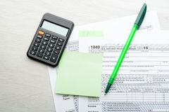 Зеленые ручка и калькулятор на налоговой форме Стоковое Фото