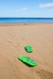 Зеленые сандалии на песчаном пляже Стоковая Фотография RF