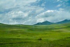 Зеленые холмы и Meadiows, белые облака и горы на горизонте Стоковые Изображения RF