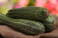 Зеленые цукини или courgettes на дерюге с запачканной предпосылкой Стоковое Фото