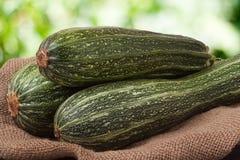 Зеленые цукини или courgettes на дерюге с запачканной предпосылкой Стоковые Изображения