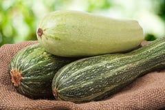 Зеленые цукини и courgettes на дерюге с запачканной предпосылкой Стоковая Фотография RF