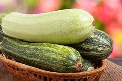 Зеленые цукини и courgettes на дерюге с запачканной предпосылкой Стоковая Фотография