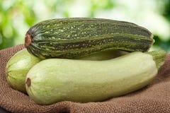 Зеленые цукини и courgettes на дерюге с запачканной предпосылкой Стоковые Изображения