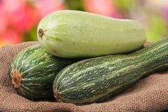 Зеленые цукини и courgettes на дерюге с запачканной предпосылкой Стоковое фото RF