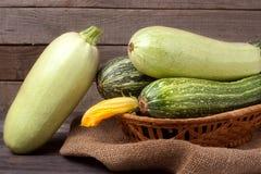 Зеленые цукини и courgettes с цветком на предпосылке дерюги деревянной Стоковое Фото