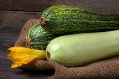 Зеленые цукини и courgettes с цветком на предпосылке дерюги деревянной Стоковая Фотография
