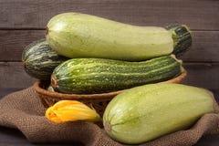 Зеленые цукини и courgettes с цветком на предпосылке дерюги деревянной Стоковые Изображения RF
