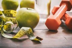 Зеленые яблоки, гантели и измеряя лента Стоковая Фотография