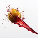 Зеленые яблоко и выплеск красного сока на белой предпосылке Стоковое Изображение