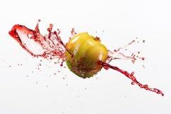 Зеленые яблоко и выплеск красного сока на белой предпосылке Стоковые Изображения RF