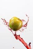 Зеленые яблоко и выплеск красного сока на белой предпосылке Стоковые Изображения